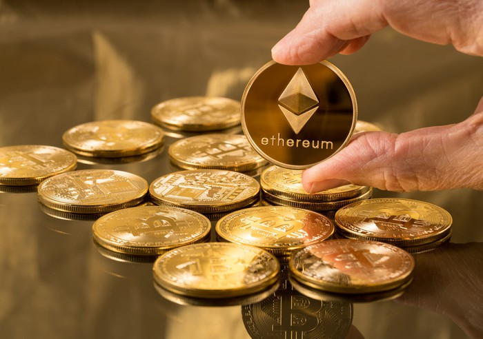 A person holding up a gold colored Ethereum coin with the logo printed on it.